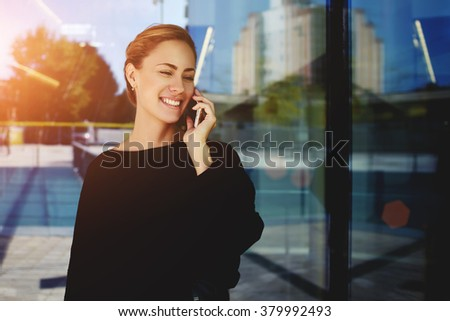 Happy female worker have pleasant mobile phone conversation with client while standing outside near office glass door, smiling businesswoman talking with partner about meeting while use cell telephone - stock photo