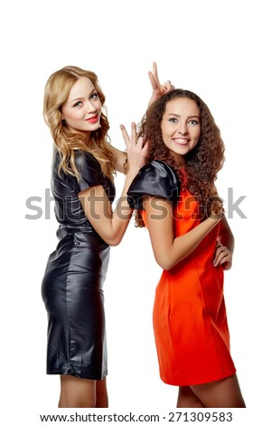 Happy females friends hugging and gesturing thumbs up, over gray background - stock photo