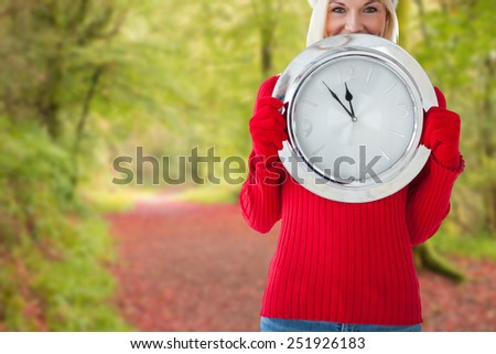 Happy festive blonde with clock against peaceful autumn scene in forest - stock photo