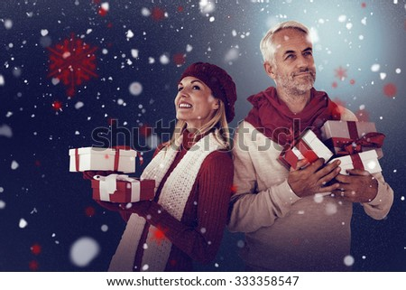 Happy festive couple with gifts against snow - stock photo