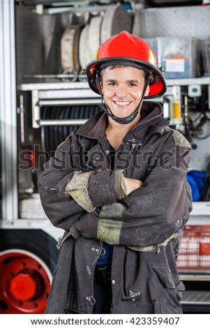 Happy Firefighter Standing Arms Crossed Against Firetruck - stock photo
