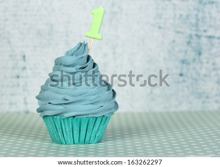 Happy first birthday cupcake with candle number 1 - stock photo