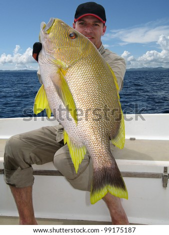 Happy  fisherman holding a beautiful Blubberlip snapper - stock photo