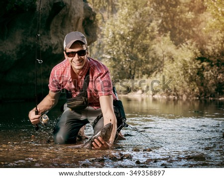 Happy fisherman holding a fish caught. Fishing on the beautiful river. - stock photo
