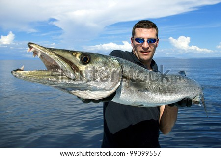 Happy  fisherman holding a giant barracuda - stock photo