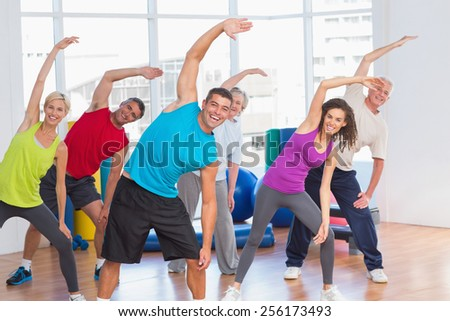Happy fit people doing stretching exercise in gym - stock photo