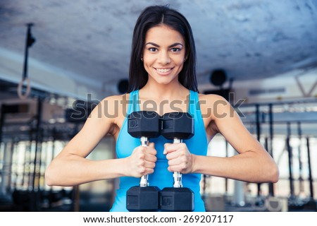 Happy fit woman holding dumbbells at gym - stock photo