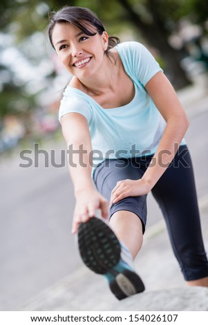 Happy fit woman stretching before running outdoors  - stock photo