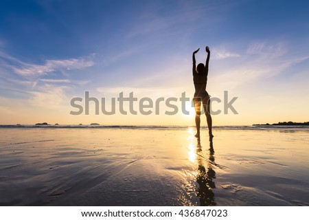 Happy fit woman stretching hands up on the beach with beautiful sunset - stock photo