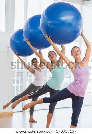 Happy fitness class and instructor doing pilates exercise with fitness balls in bright room - stock photo