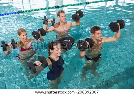 Happy fitness class doing aqua aerobics with foam dumbbells in swimming pool at the leisure centre - stock photo