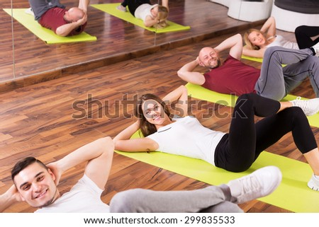Happy fitness coach showing to adult learners new exercise at class - stock photo
