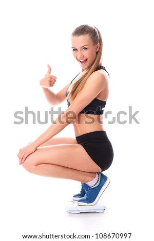 Happy fitness girl on the scales with thumb up over white background - stock photo