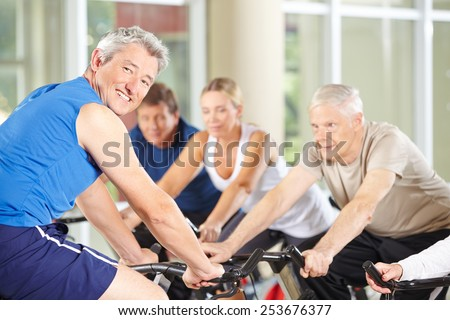Happy fitness trainer with senior group on spinning bikes in gym - stock photo