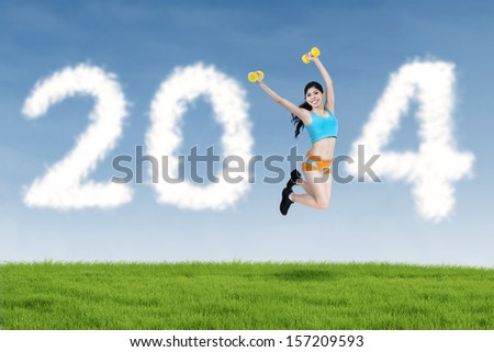 Happy fitness woman jumping and 2014 New Year clouds outdoor - stock photo