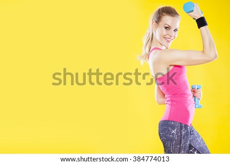 Happy fitness woman with dumbbells on isolated yellow background - stock photo