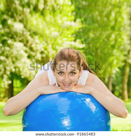 Happy fitness woman with pilates ball outdoors. - stock photo