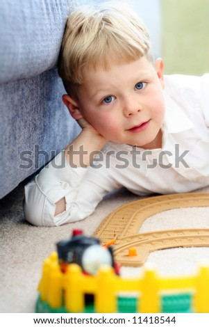 Happy five year old boy playing with his train set - stock photo