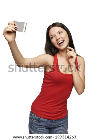 Happy flirting young girl taking pictures of herself through cell phone, over white background - stock photo