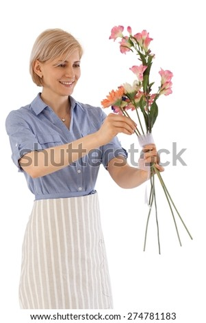 Happy florist making a bouquet of flowers. - stock photo