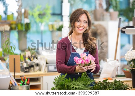Happy Florist Making Bouquet Of Pink Roses In Shop - stock photo
