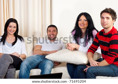 Happy four friends having a meeting in a house and sitting together on couch - stock photo