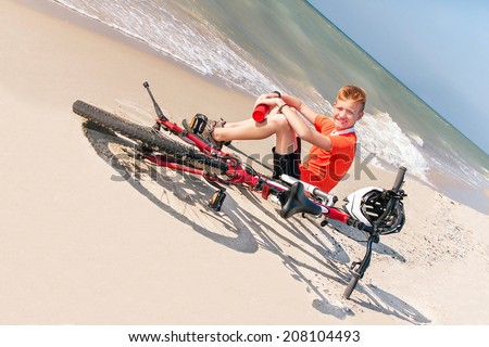 Happy free teen is sitting with bicycle on a background of the sea. Caucasian boy having fun and enjoying nature. Young active male model. Summer day. Freedom, travel (vacation) concept. Copy space.  - stock photo
