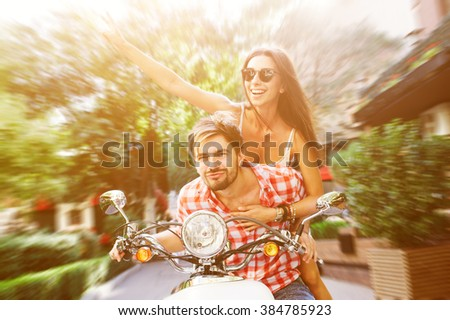 Happy freedom couple driving  retro scooter excited on summer holidays vacation. Speed blur and having fun concept - stock photo