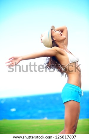Happy freedom woman in summer standing with arms out in blissful elated happiness during summer vacation travel. Multiracial asian caucasian fashion hipster wearing hat outdoor. - stock photo