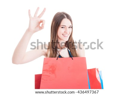 Happy friendly girl doing shopping and showing ok sign and holding paper bags with copyspace isolated on white - stock photo