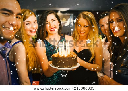 Happy friends celebrating brithday one holding birthday cake against snow - stock photo