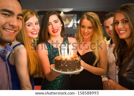 Happy friends celebrating brithday one holding birthday cake looking at camera in a nightclub - stock photo