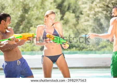 Happy friends doing water gun battle near swimming pool - stock photo