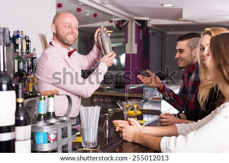 Happy friends drinking and chatting with barman at bar counter - stock photo