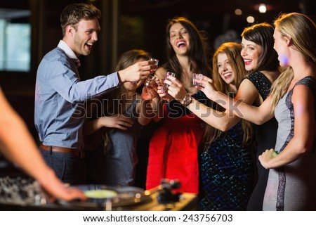 Happy friends drinking shots by the dj booth at the nightclub - stock photo