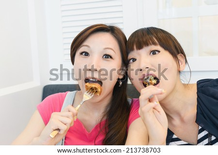 Happy friends eating in a restaurant. - stock photo