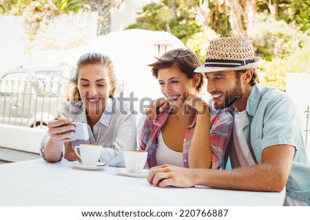 Happy friends enjoying coffee together outside at the coffee shop - stock photo