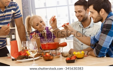 Happy friends enjoying time together, having cheese fondue, smiling. - stock photo