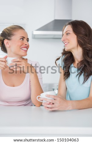 Happy friends having cups of coffee in the kitchen - stock photo