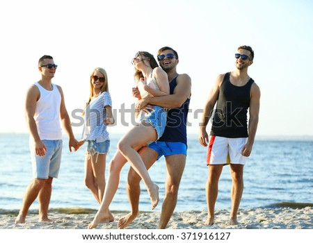 Happy friends having fun at the beach, outdoors - stock photo
