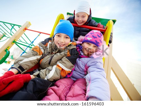 Happy friends having fun on playground in winter - stock photo