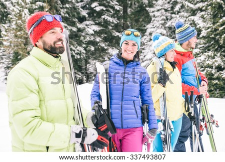 Happy friends having fun on the snow. Group of skiers walking together - stock photo