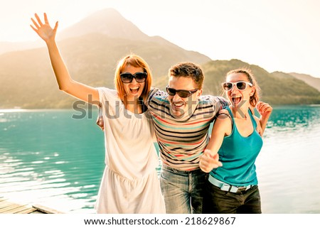 Happy friends having fun together during a sunny day on Lake. - stock photo