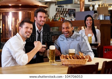 Happy friends having leisure in pub watching sport in TV together drinking beer cheering for team. - stock photo