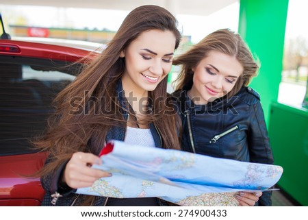 Happy friends holding map in gas station. Holiday trip of friends - stock photo