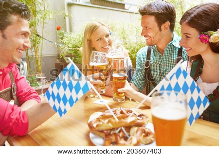 Happy friends in bavarian beer garden drinking beer in summer - stock photo