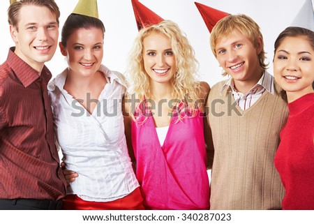 Happy friends in birthday caps looking at camera - stock photo