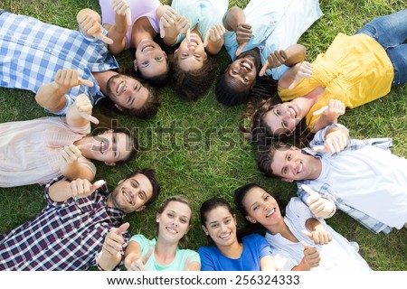 Happy friends in the park lying in circle on a sunny day - stock photo