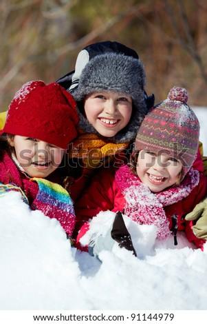 Happy friends in winterwear playing in snowdrift outside - stock photo