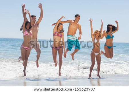 Happy friends jumping on the beach against ocean on holidays - stock photo